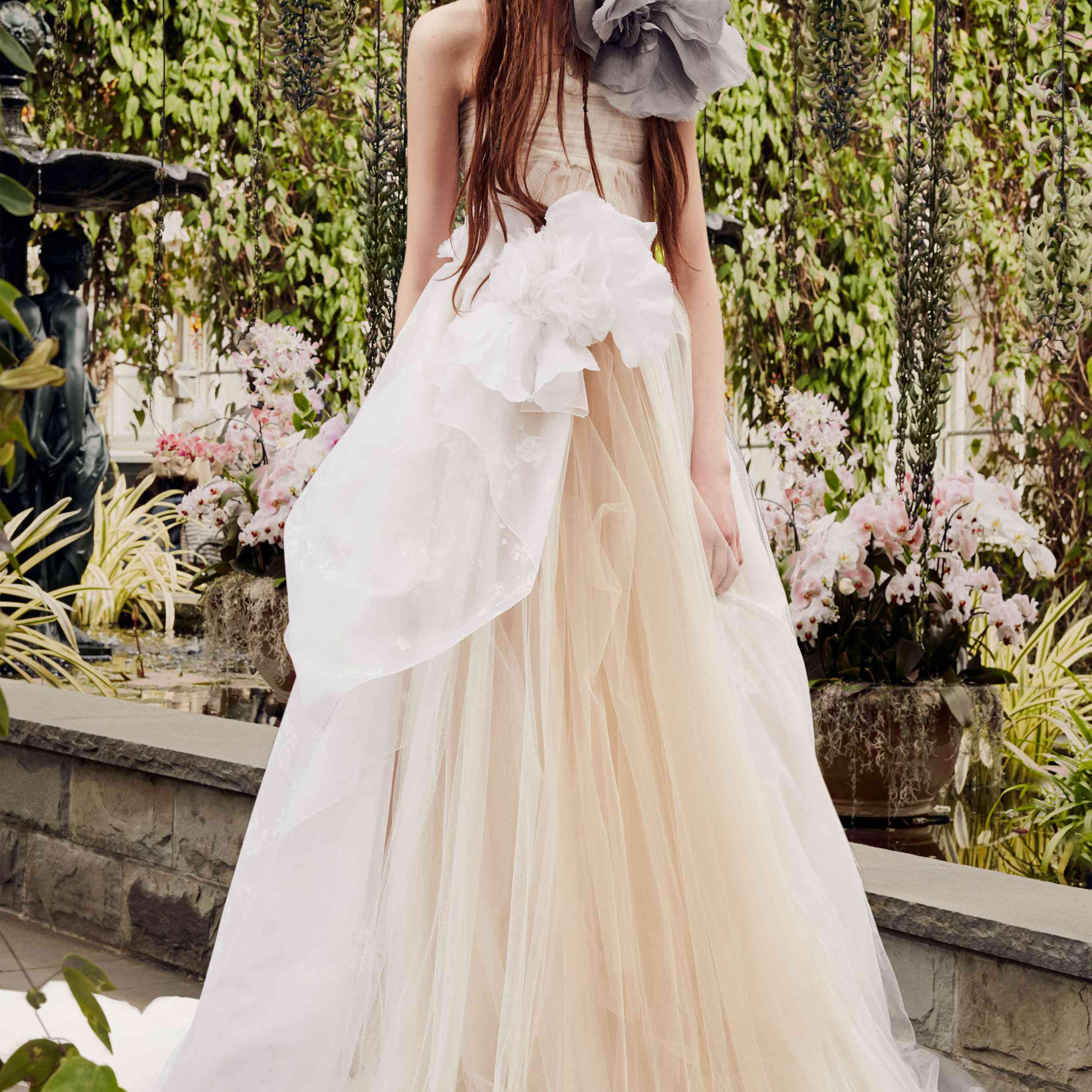 Model in nude tulle one-shoulder A-line gown with a white flower detail at the waist and a gray flower detail at the shoulder