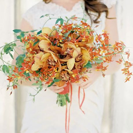 Lush bridal bouquet comprised of orange cymbidium orchids and greenery