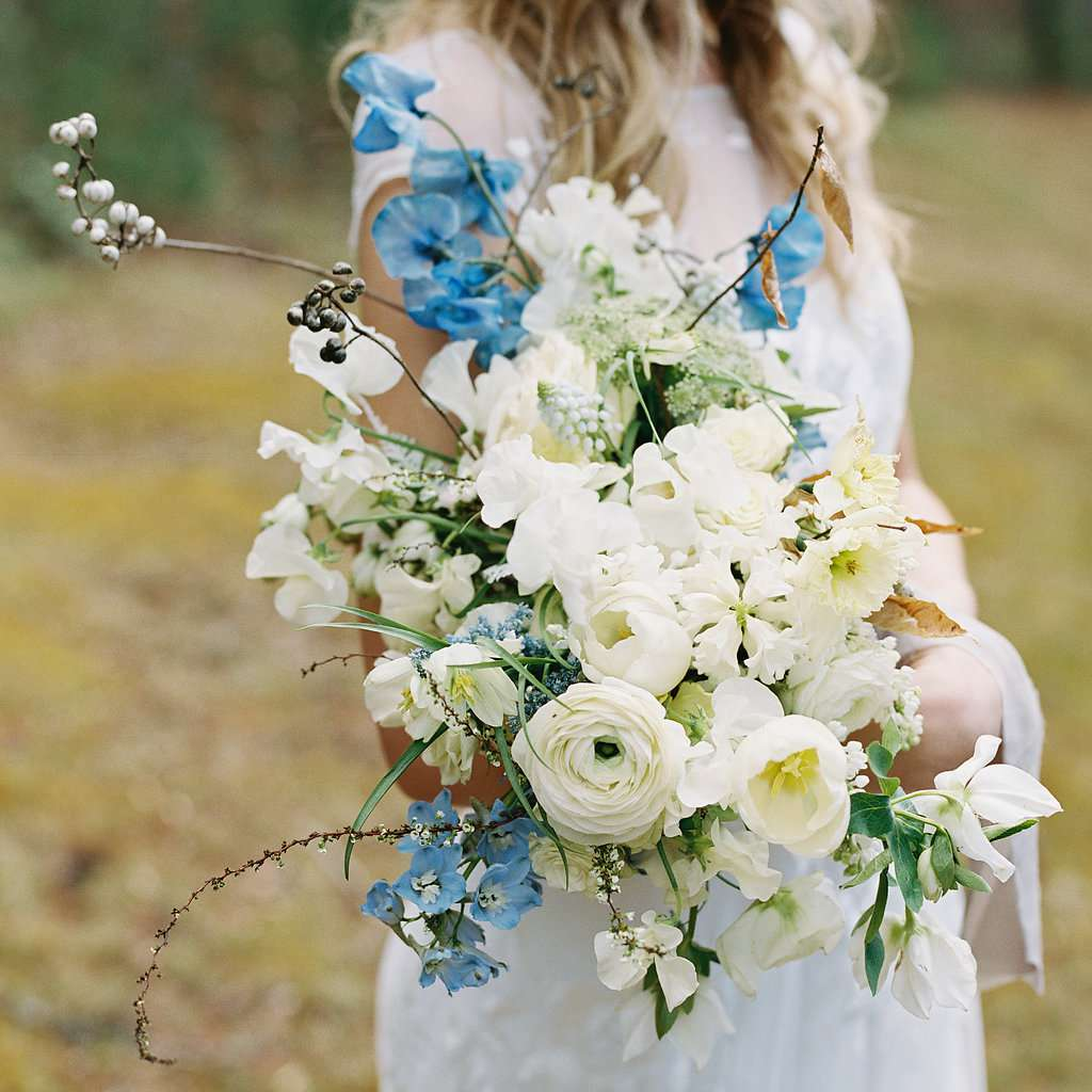 Bride holding a bouquet of tulips, ranunculus, and sweet pea