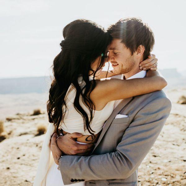 Bride and groom embracing in desert.