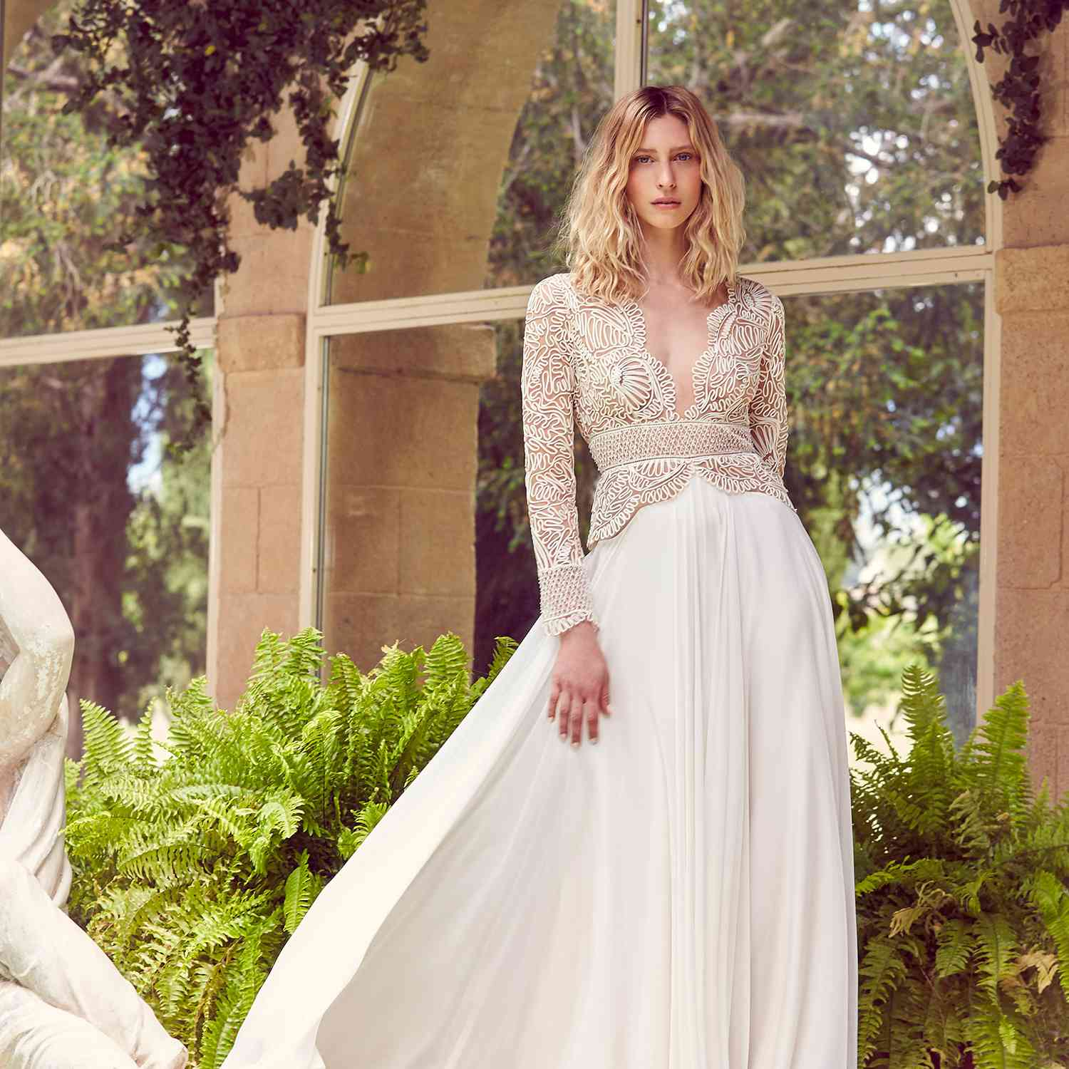 Model in wedding gown with embroidered illusion bodice and neckline