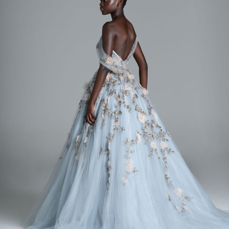 Model in blue ballgown with asymmetrical off-the-shoulder neckline and 3D floral embroidery