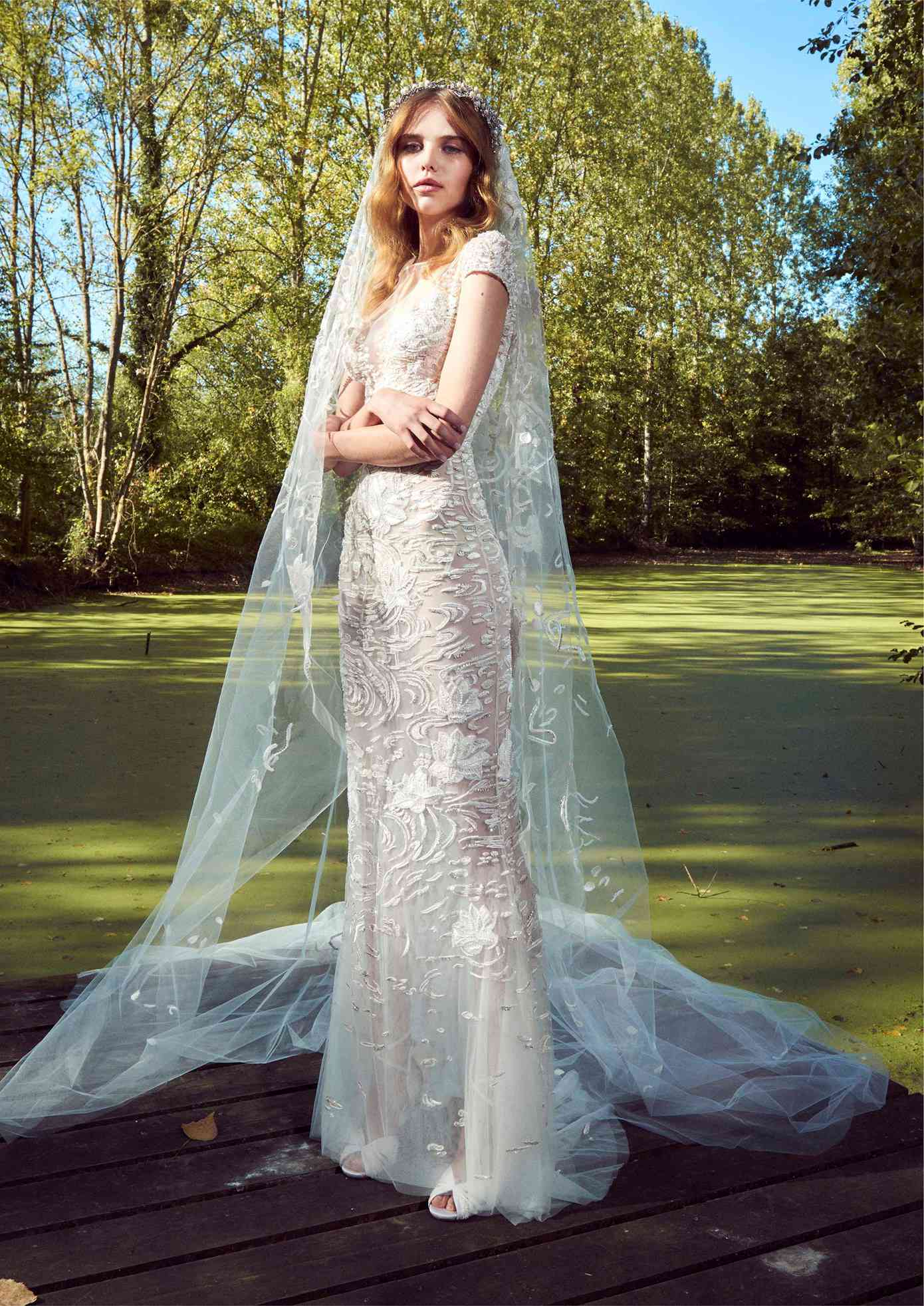 Model in a tulle sheath gown with cap sleeves, an illusion neckline, 3D beaded embroidery, and a matching veil