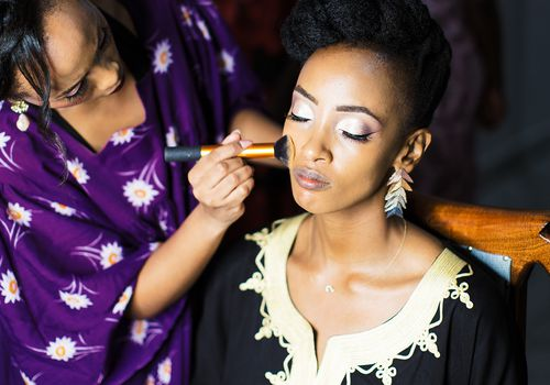 Woman applying powder face makeup onto a bride on her wedding day