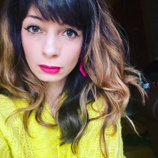 Nicole Briese wears a neon yellow sweater and hot pink lipstick