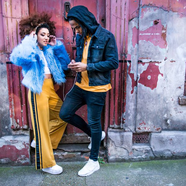 Couple leans against building, listening to music via headphones
