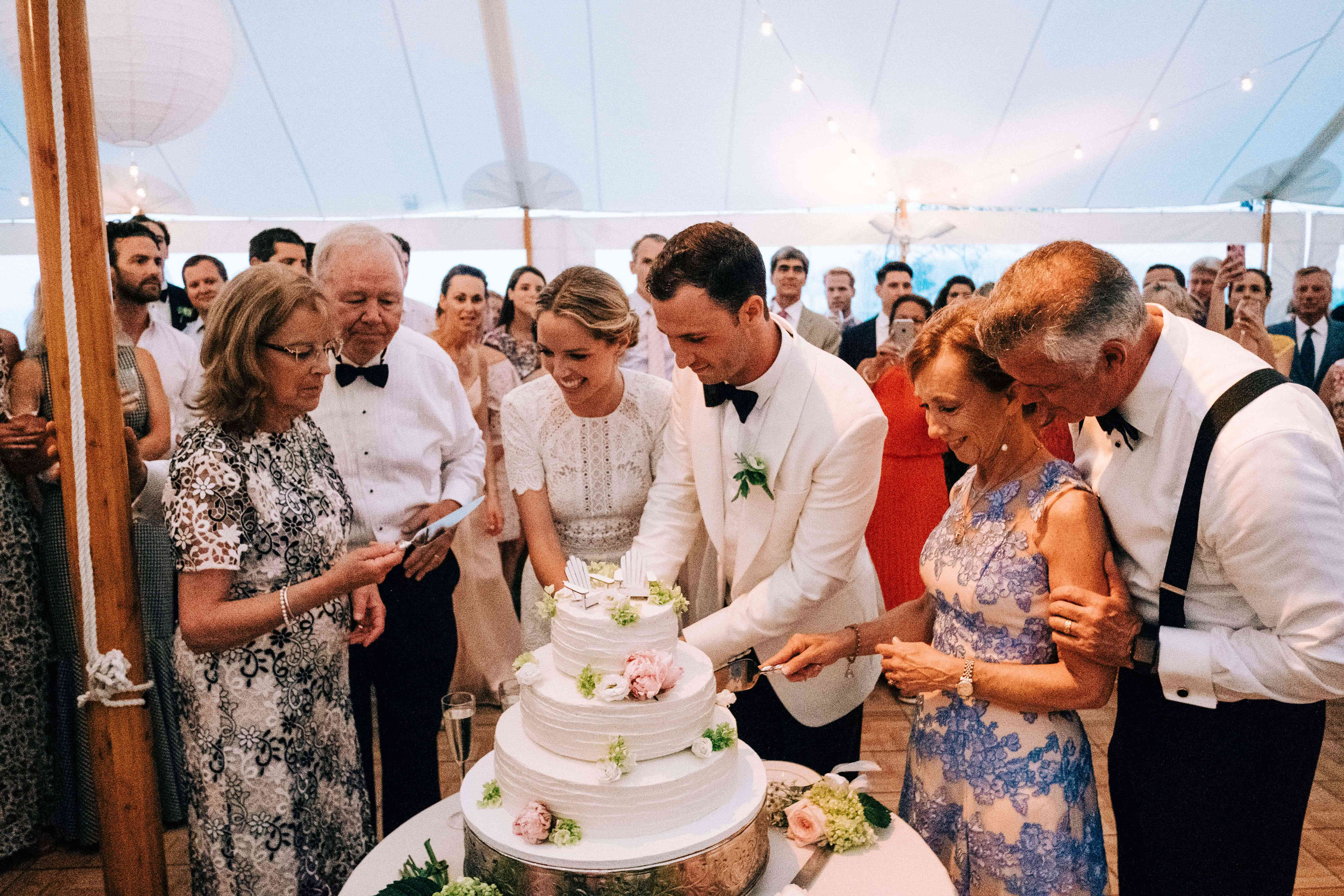 <p>couple cutting cake with their parents</p><br><br>