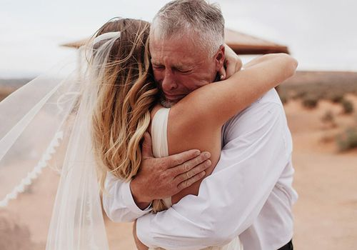 dad and bride hugging