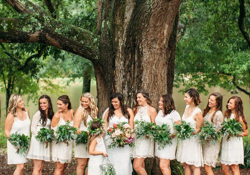 Bride, bridesmaids, and flower girl posing under a tree.
