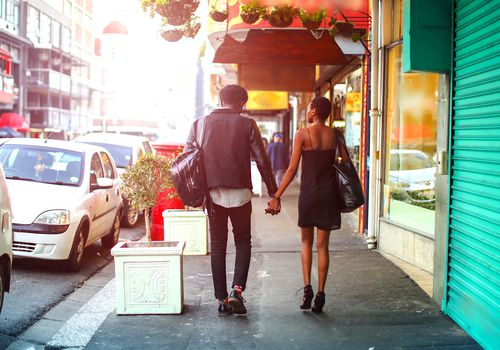 man and woman walking down a city street holding hands