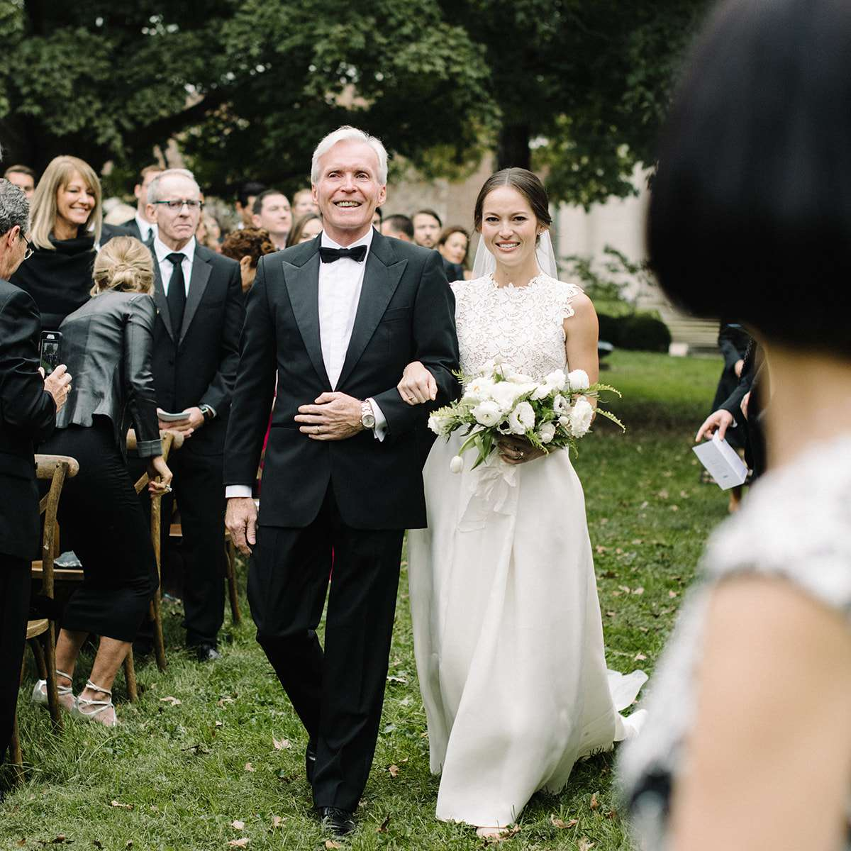 The bride and her father walk up the aisle.