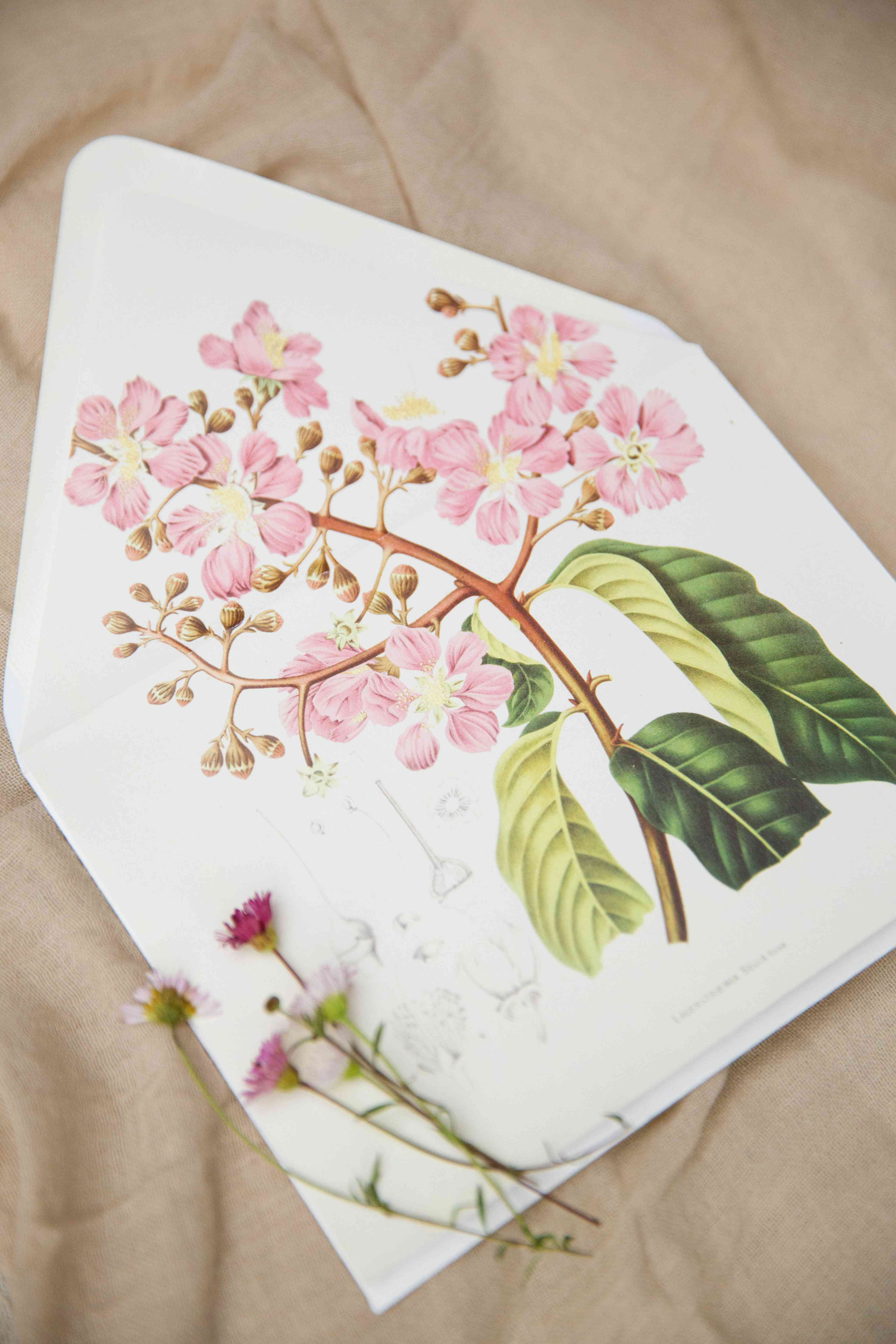 A wedding invitation envelope with a pink flower print