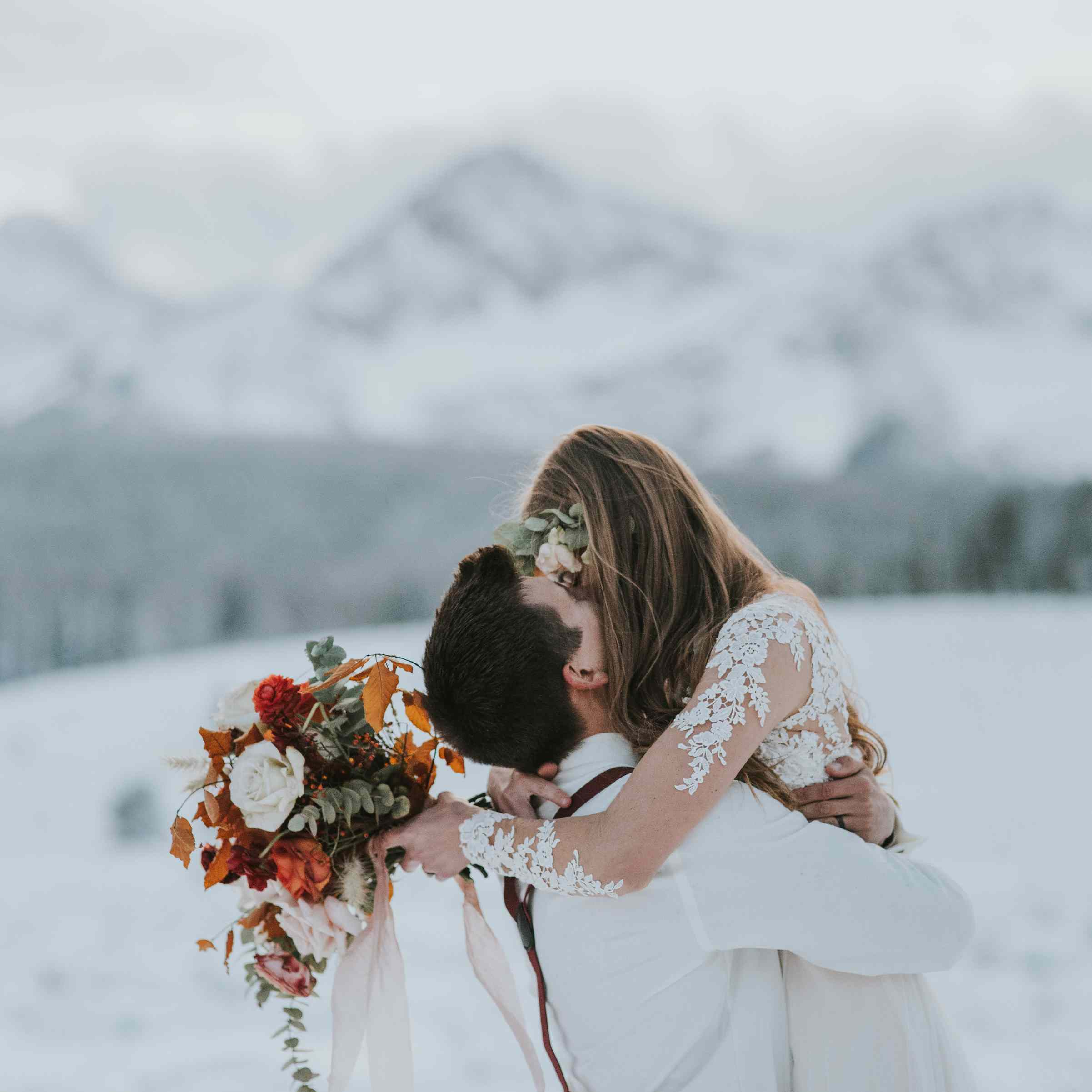 Groom holding bride outside with mountains in the background