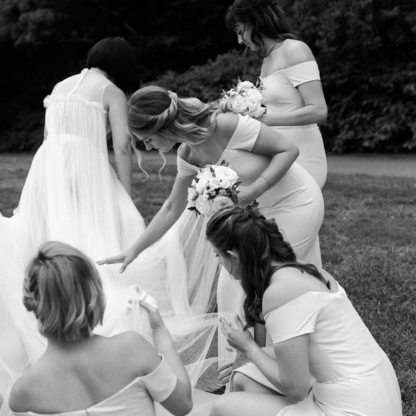 Bridesmaids helping bride with train