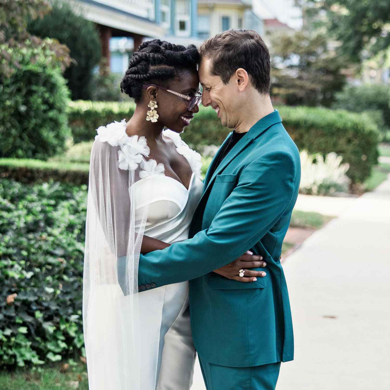 Bride in groom in green suit embracing