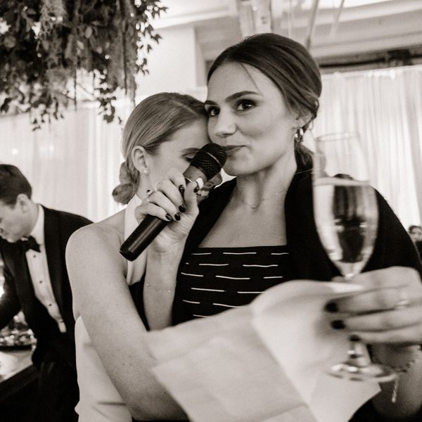 Woman giving a speech at a wedding while bride hugs her