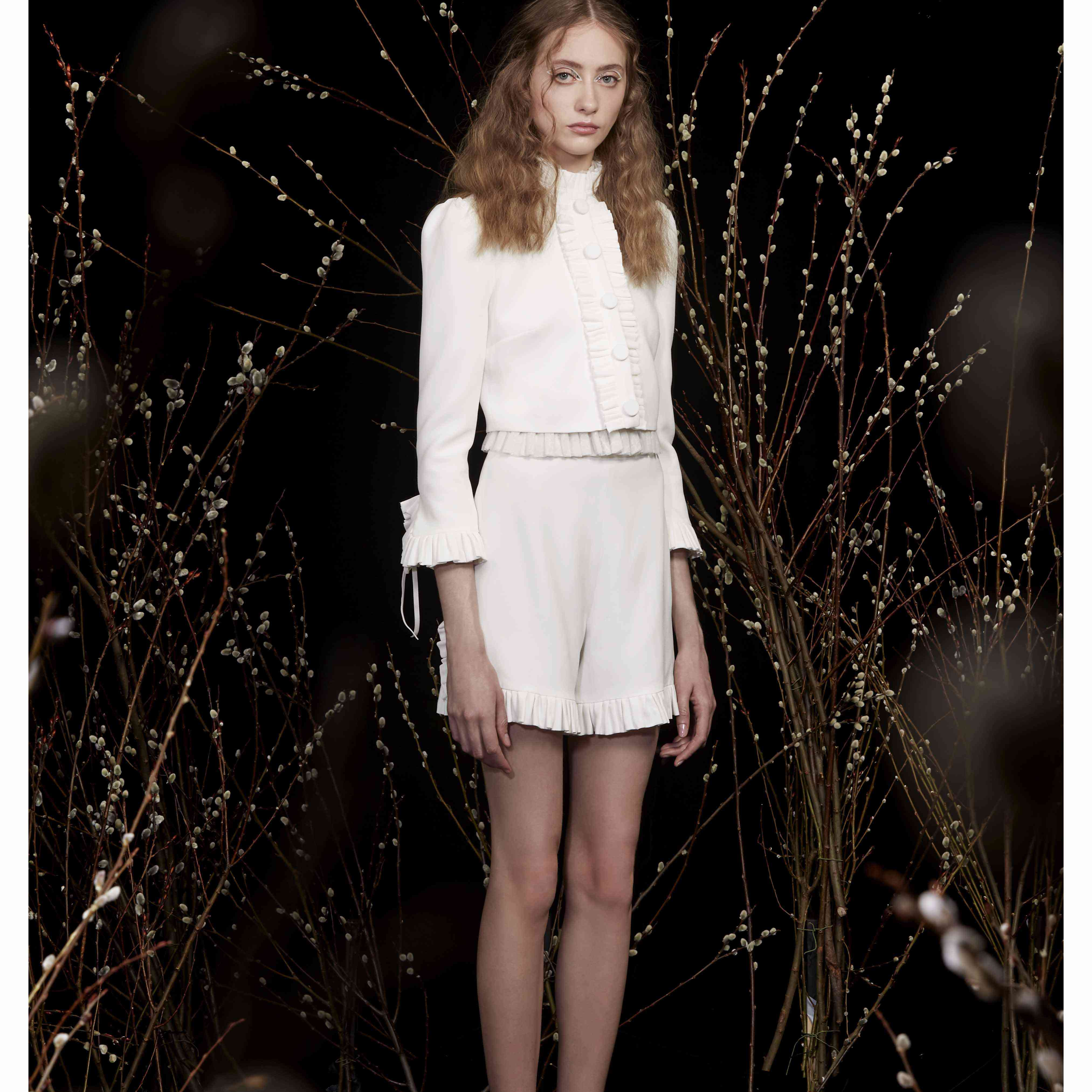 Model in crop wedding jacket and shorts
