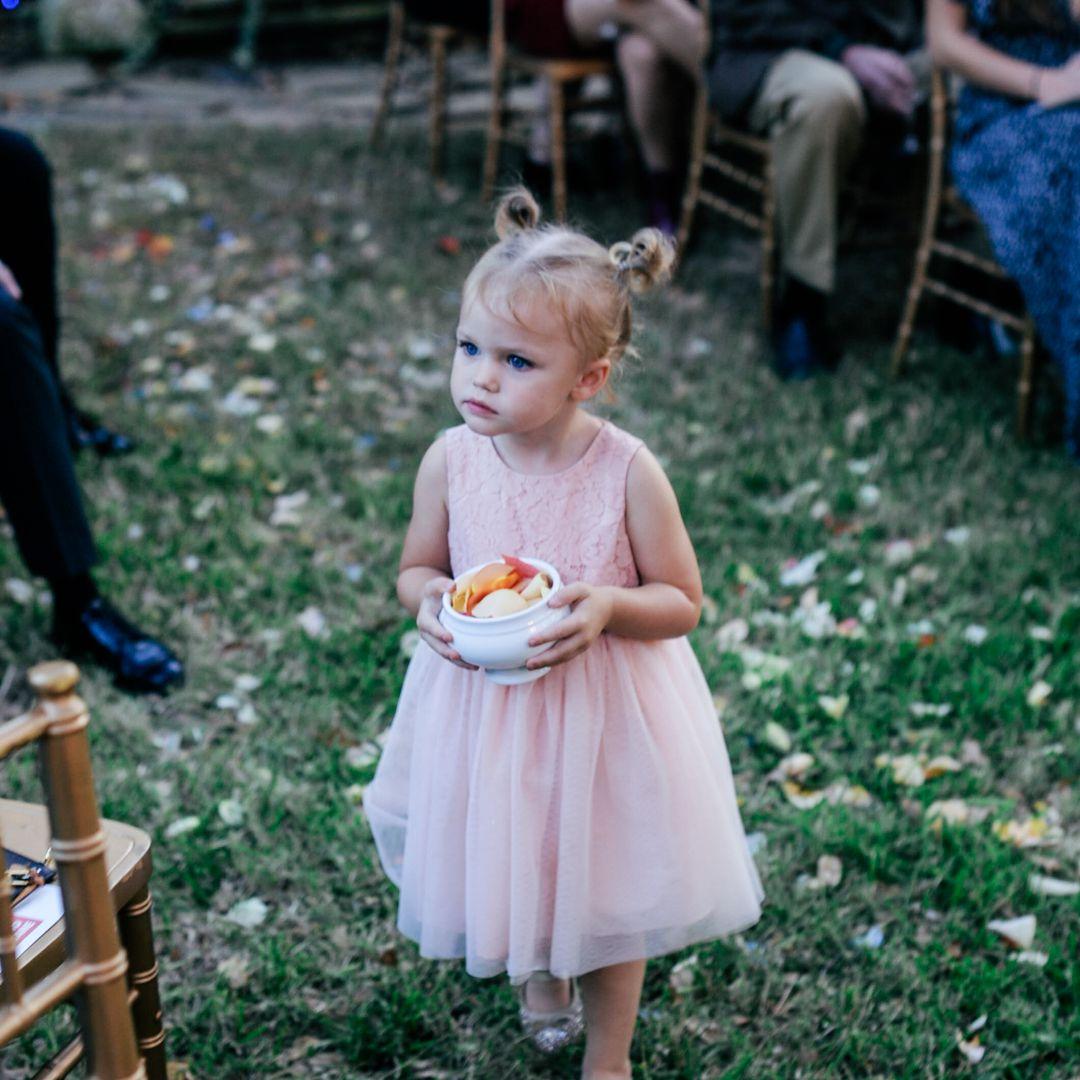 Flower girl holding petals