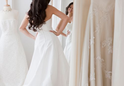 bride trying on wedding dress