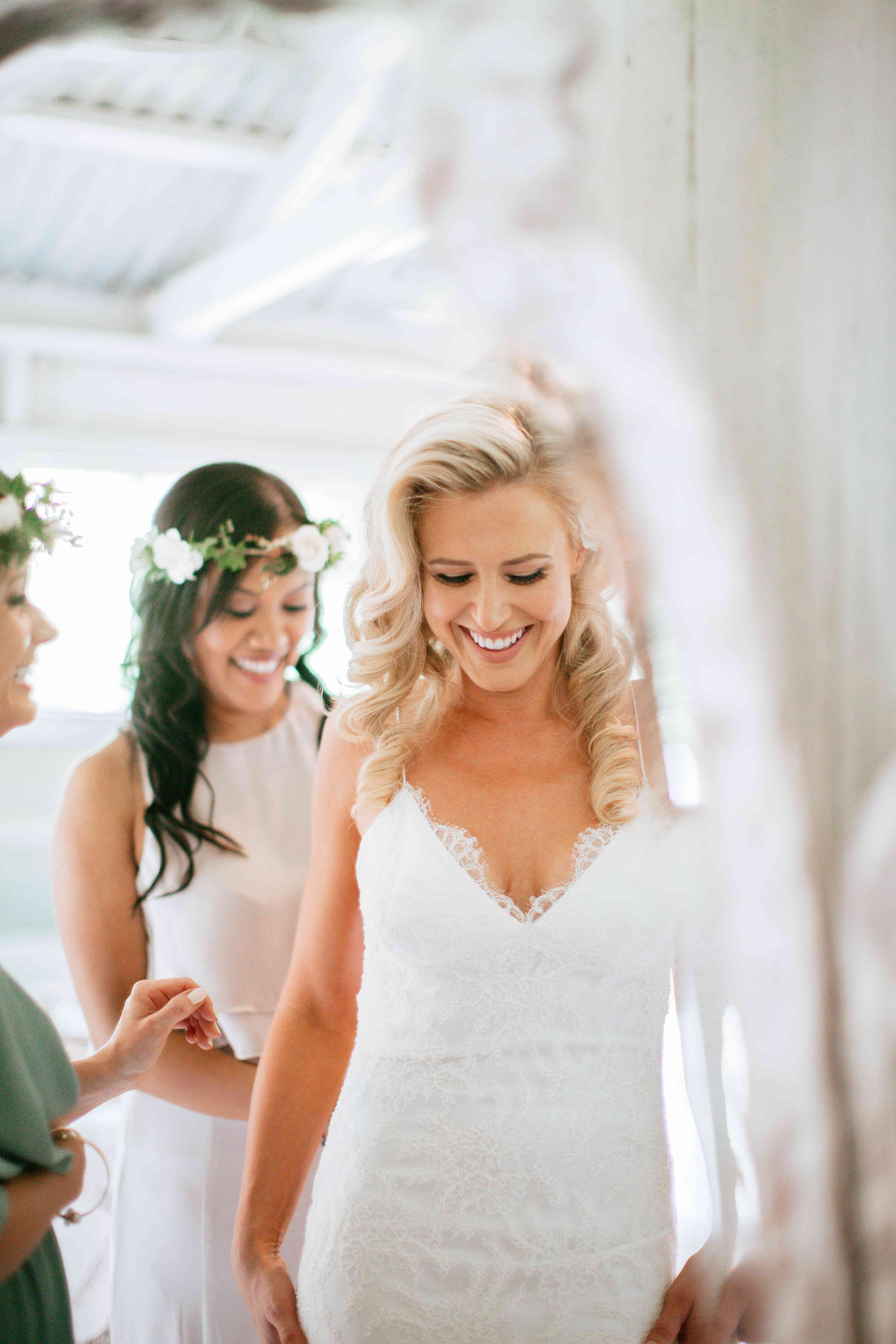 Bride in mirror getting ready with bridesmaids