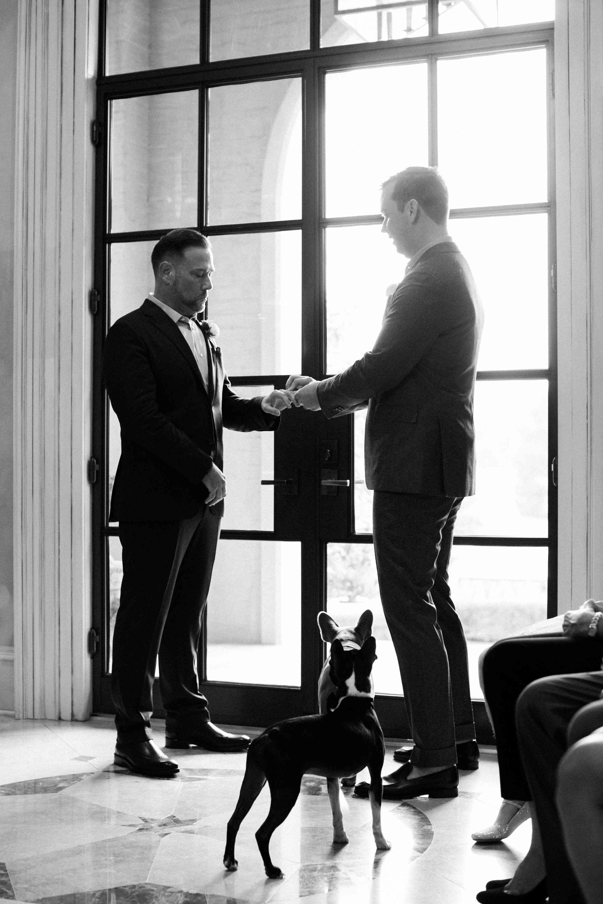 Grooms exchanging rings with dogs at their feet