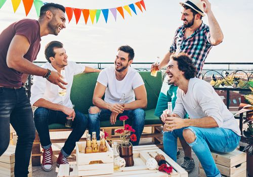 Group of men drinking beer and laughing on rooftop