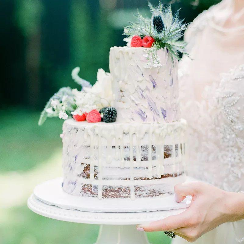 Bright white naked wedding cake with white chocolate drip