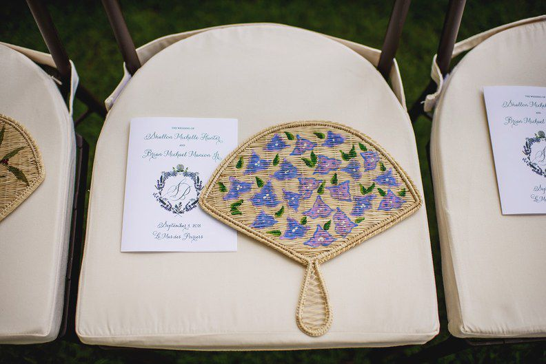 Hand-painted custom fan on a chair at an outdoor wedding beside a program