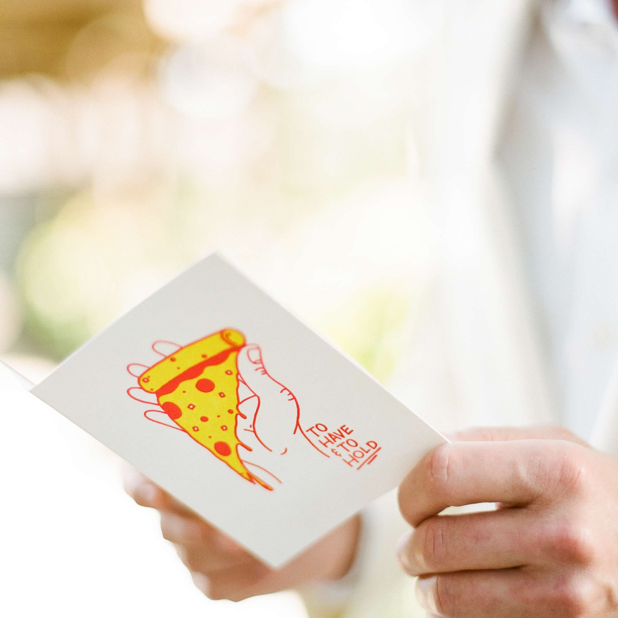 Person reading a card with a picture of a slice of pizza on the front that says