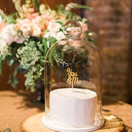 A single-tiered white wedding cake complete with a laser-cut cake topper