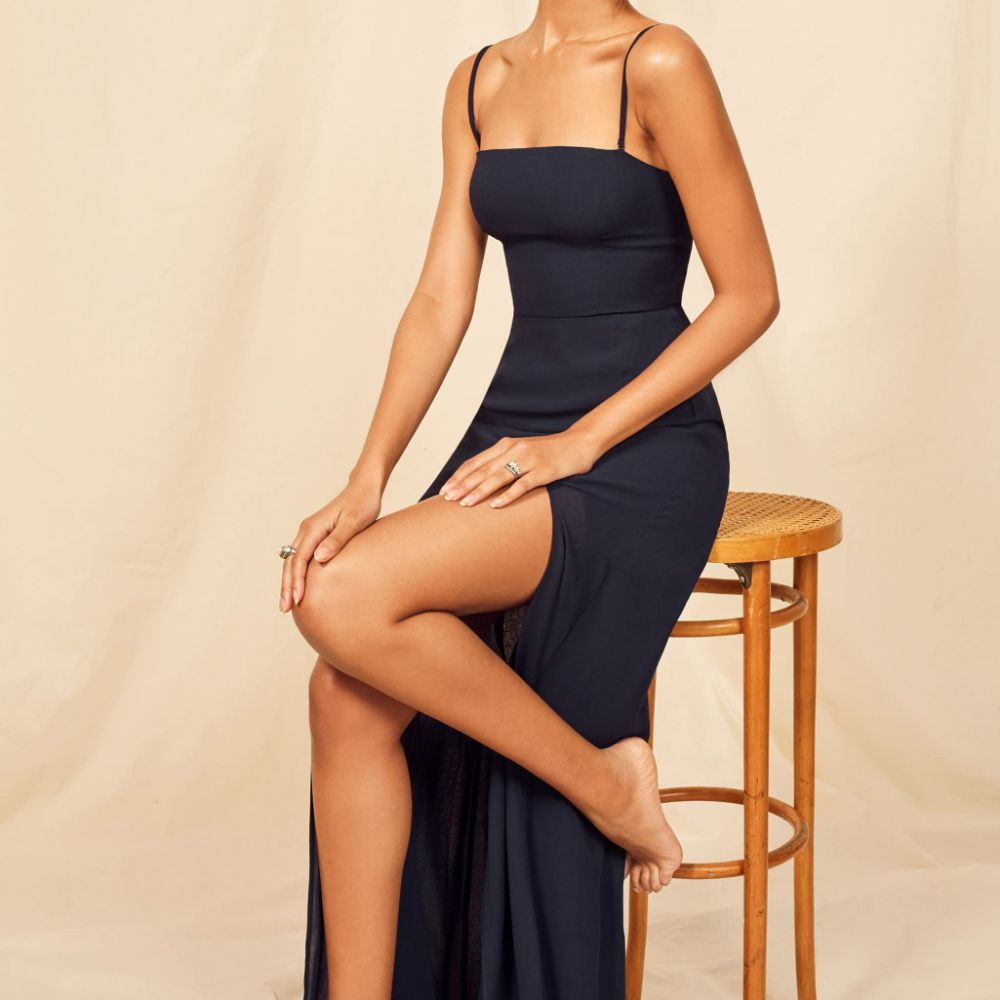 Model in a spaghetti strapped dark blue floor-length dress with a skirt slit
