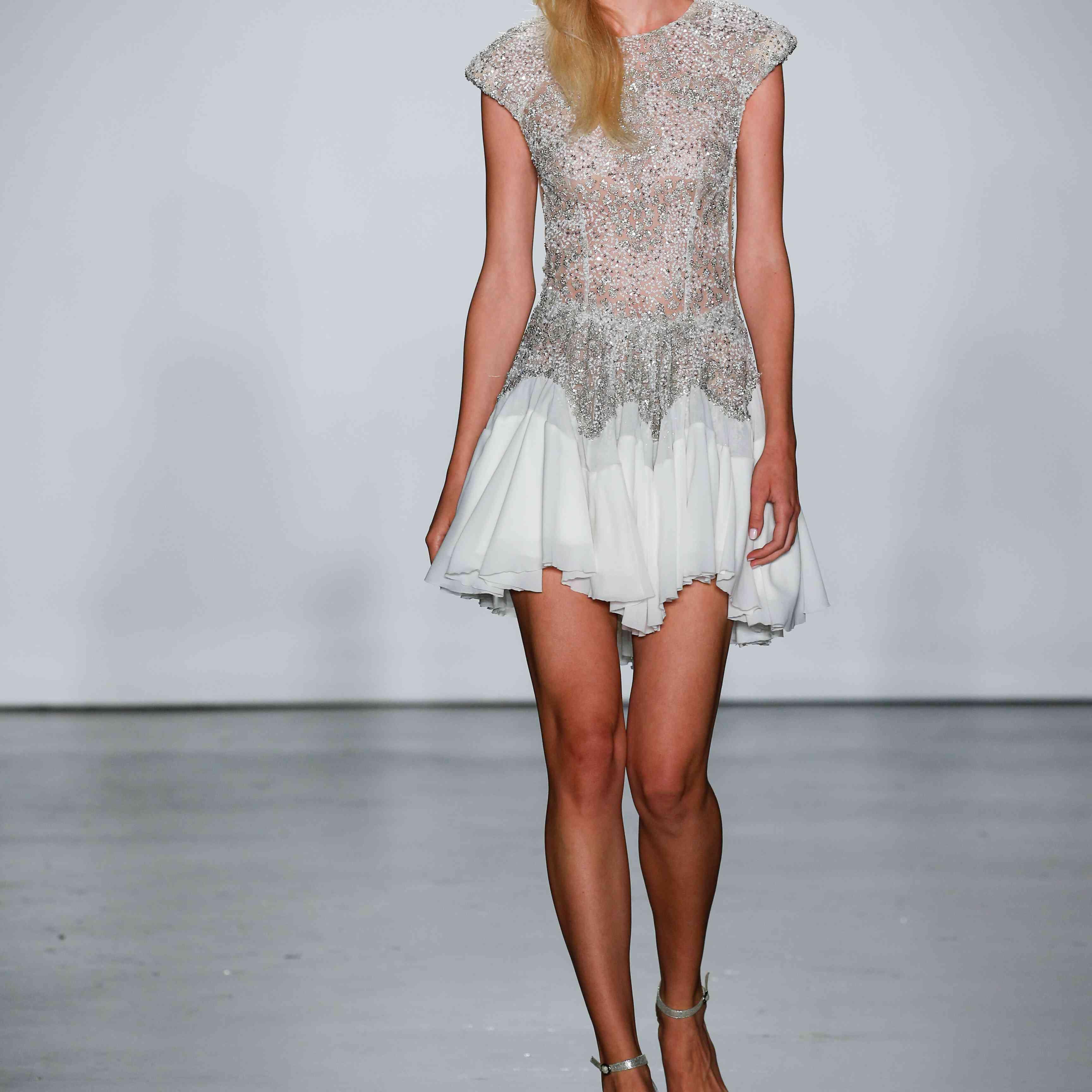 Model in low back mini wedding dress