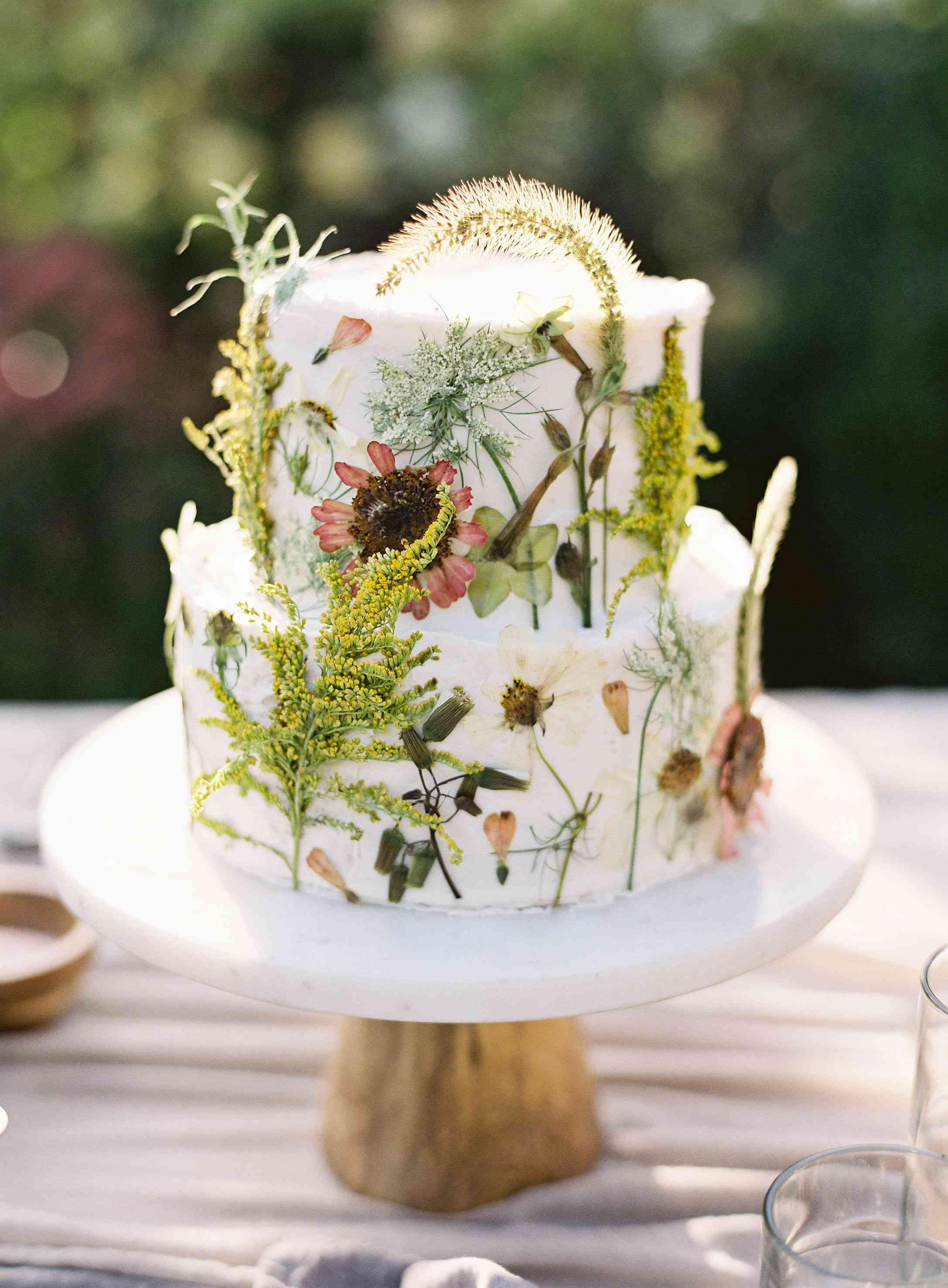 Two-tiered white wedding cake covered in dried flowers