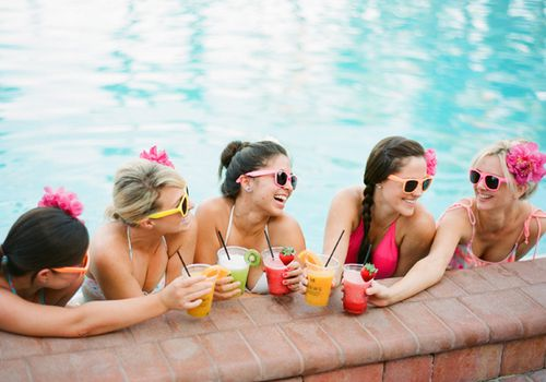 Five women smiling and holding colorful drinks while in a pool