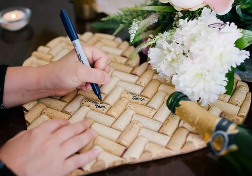 Signing wine corks as guest book