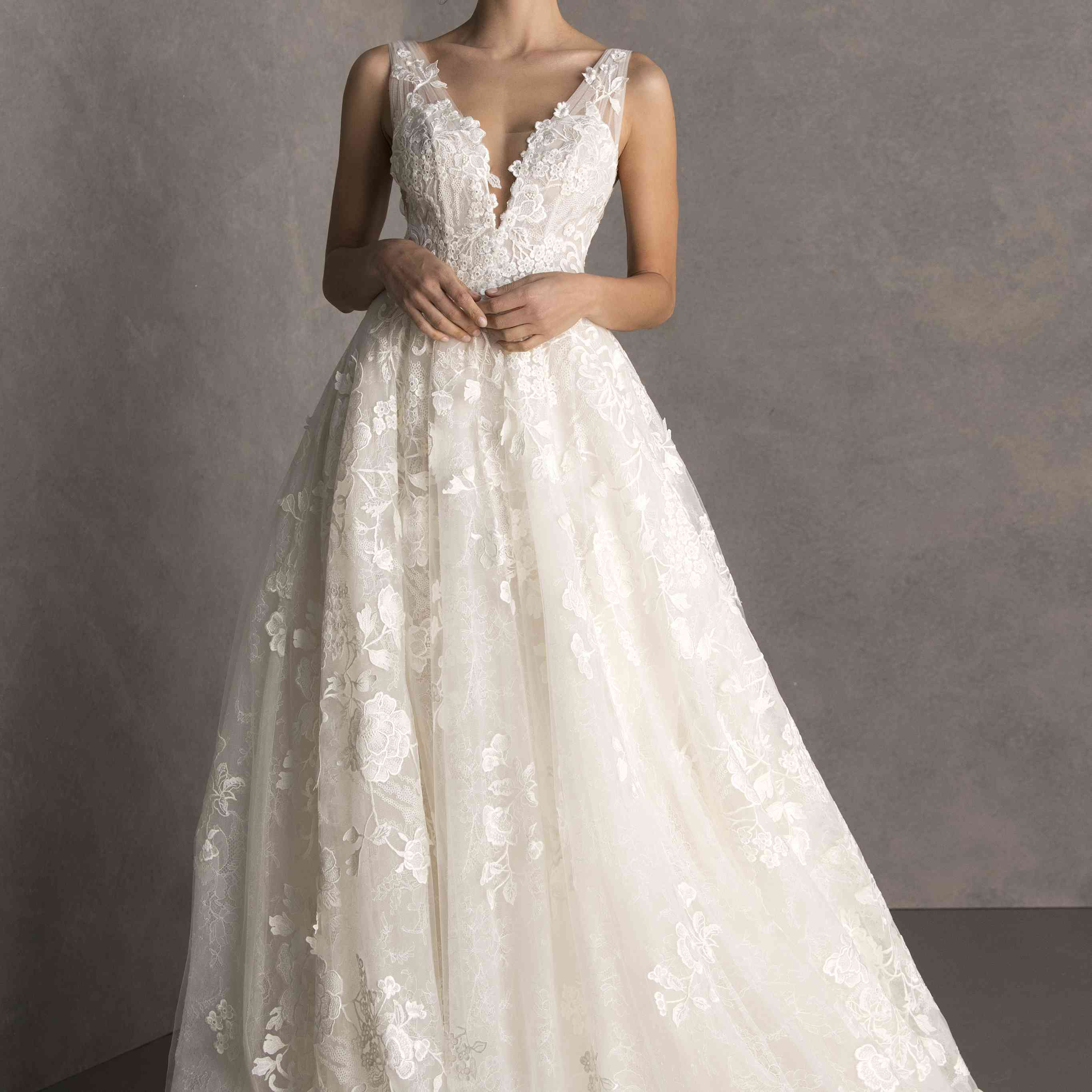 Model in floral-embroidered ballgown with plunging illusion neckline