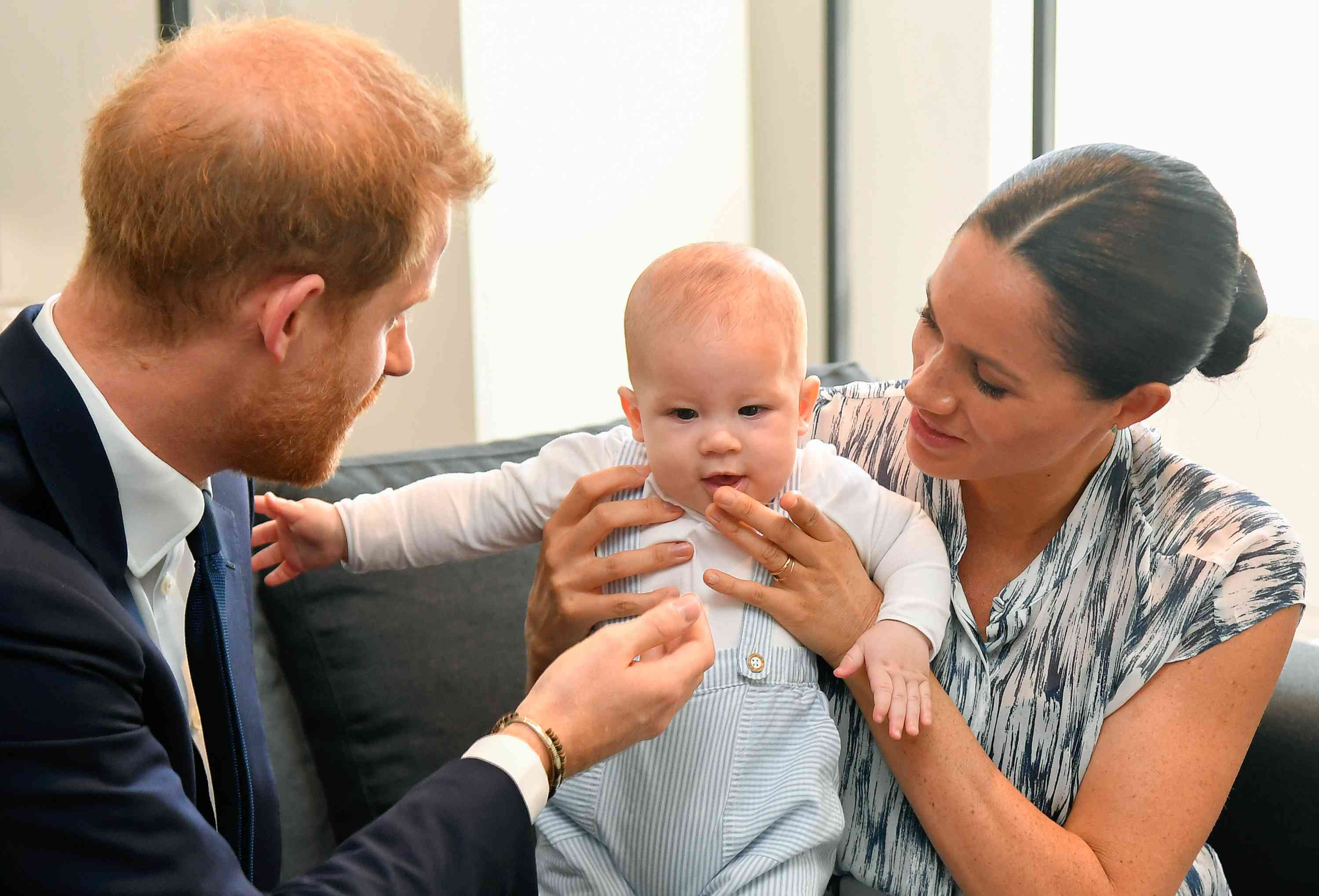 Prince harry and meghan markle holding baby