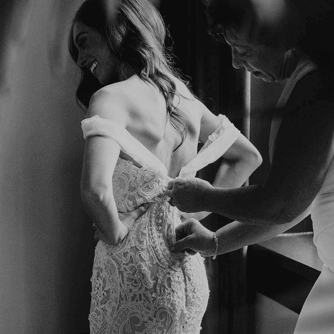 mom zipping bride's dress