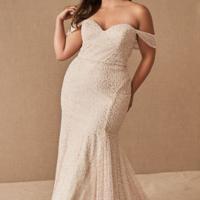 Plus size model in sparkly fit and flare off the shoulder gown