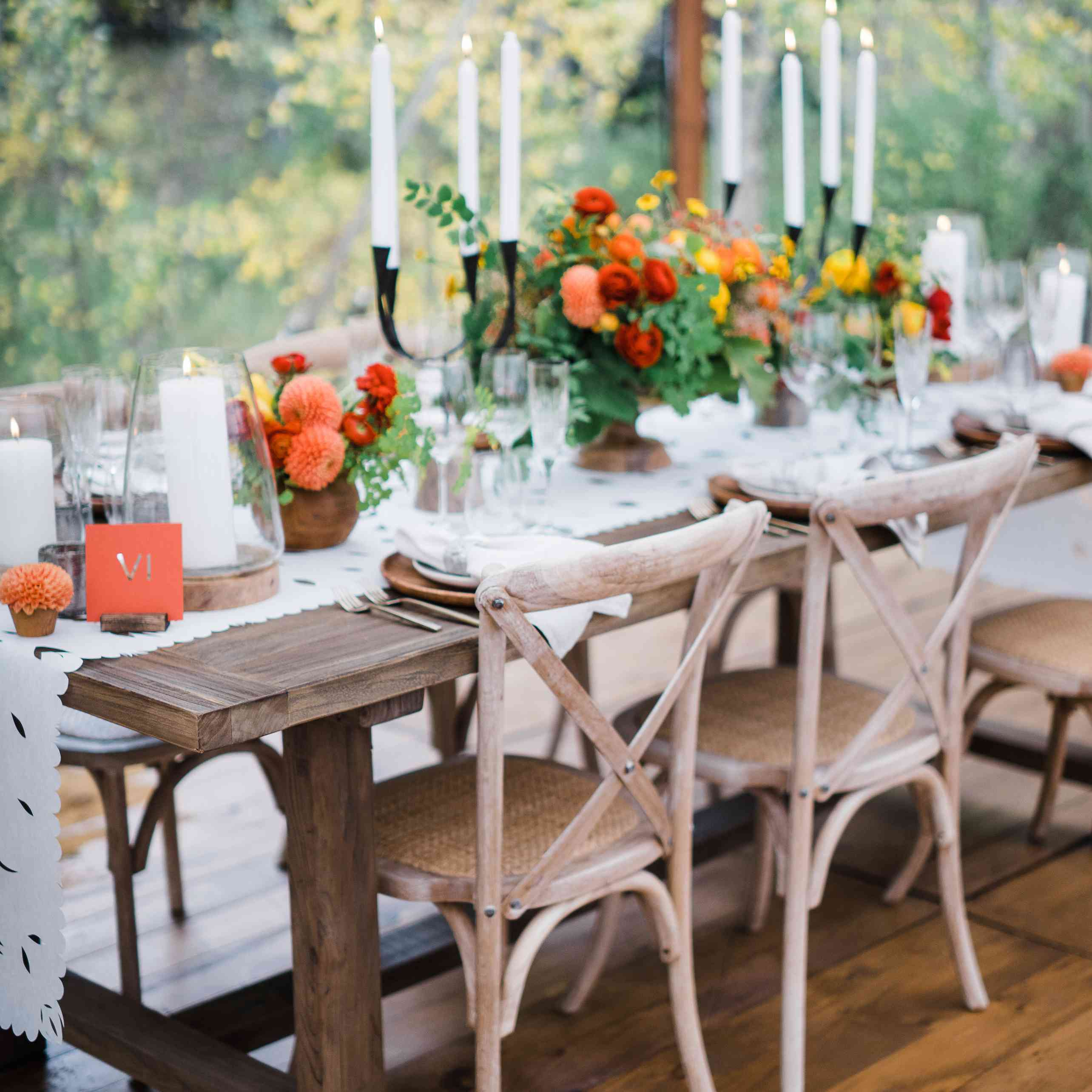 Natural wood wedding reception seating with candles and floral décor