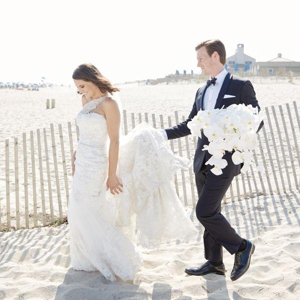 Bride and groom walking in sand