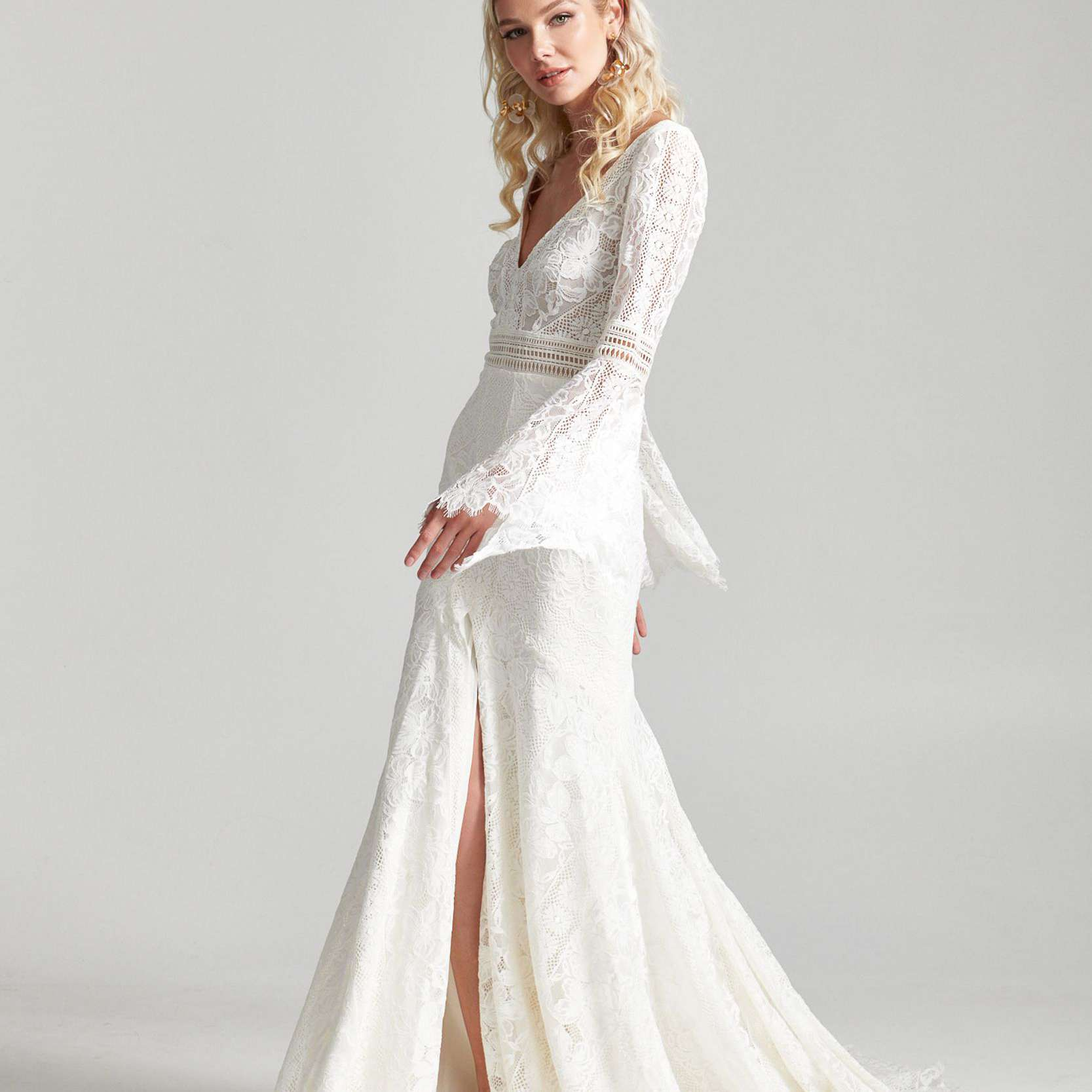 Model in lace wedding dress with long bell sleeves and skirt slit
