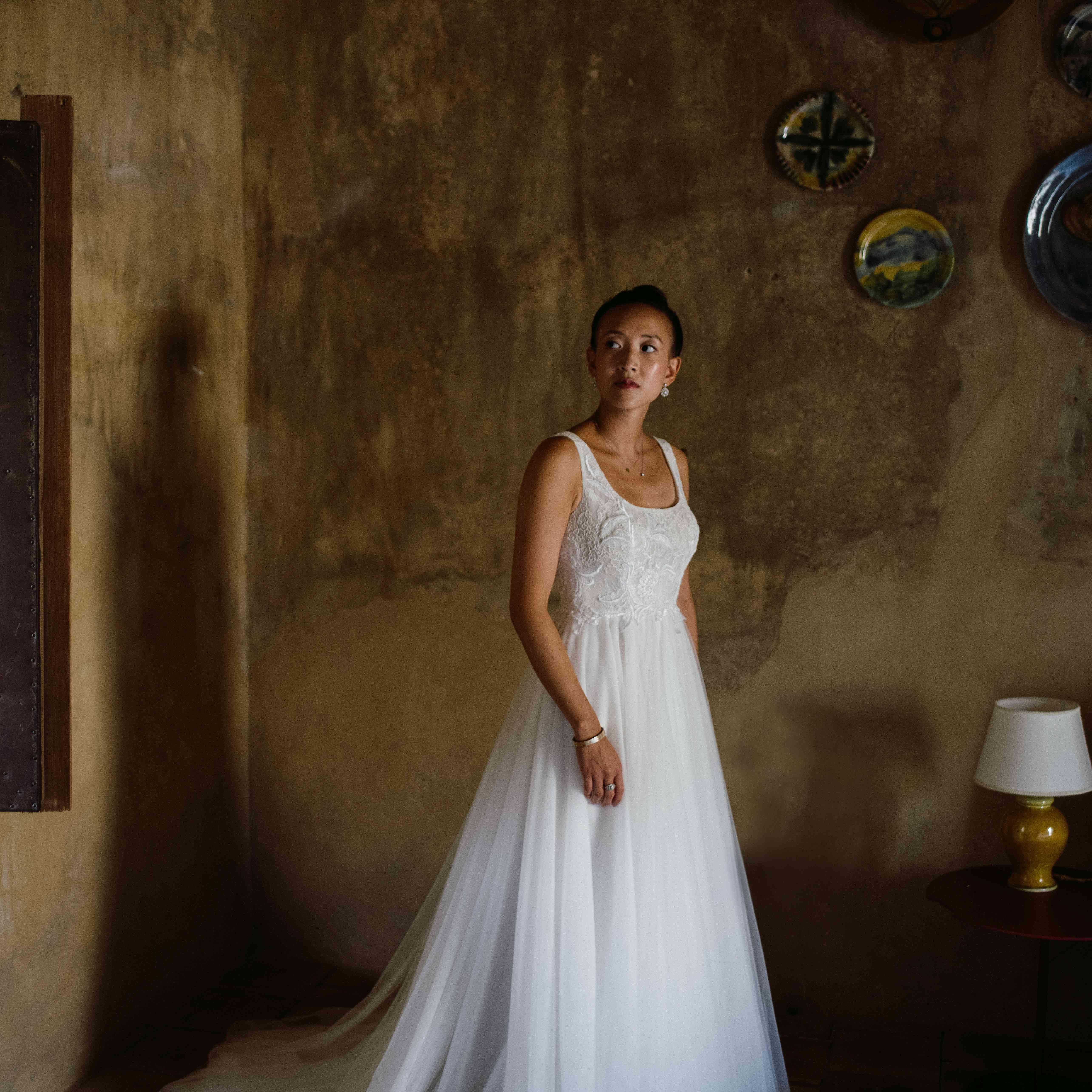 Bride standing in a room in her wedding gown
