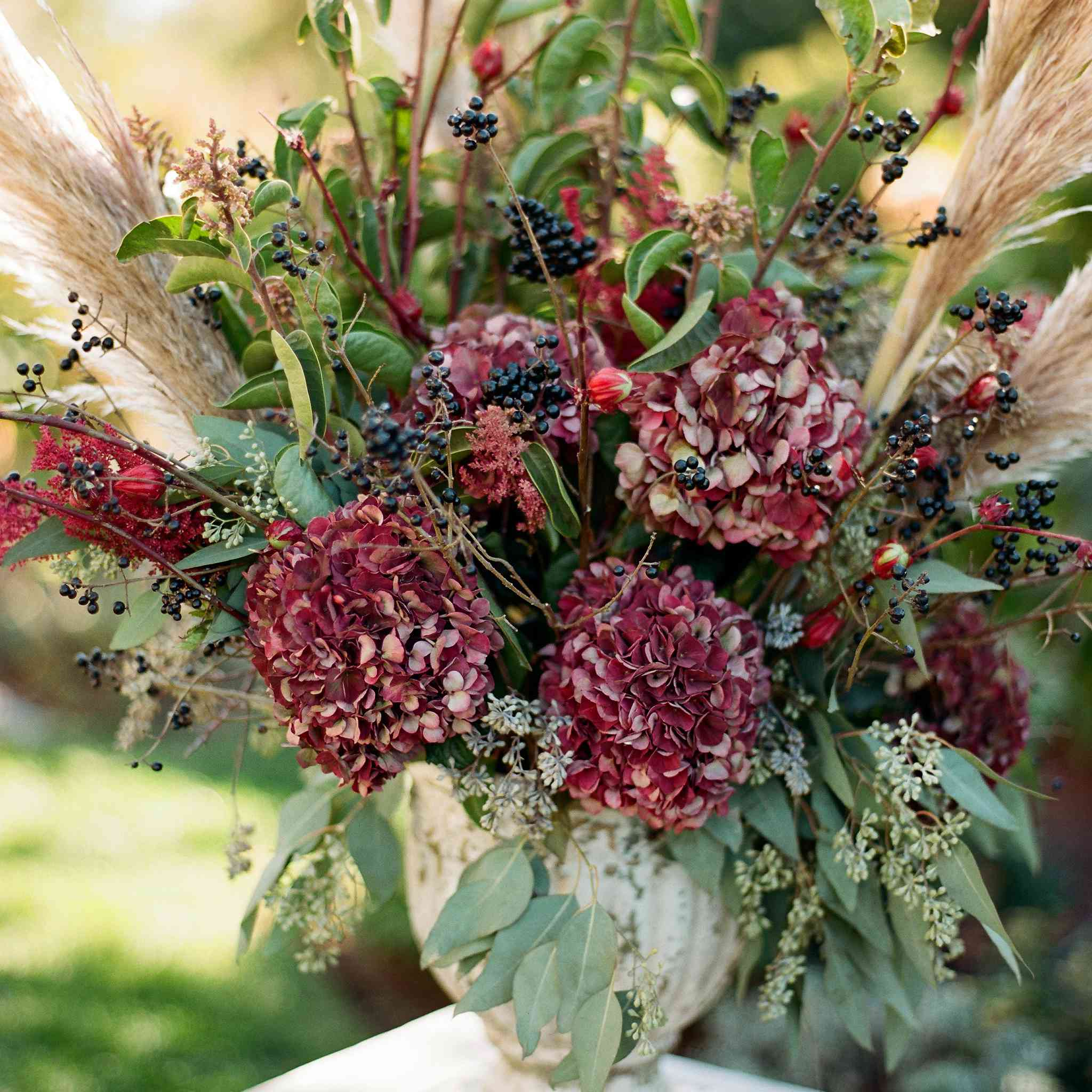 <p>burgundy flowers in urns</p><br><br>