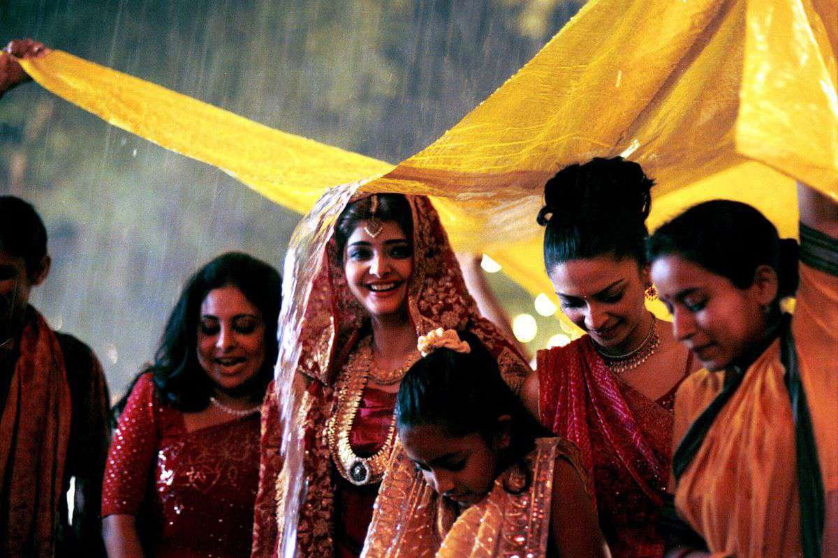 Several Indian women standing under a tarp at a wedding while it rains, still from