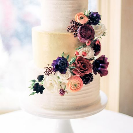 A three-tiered white wedding cake adorned with a flourish of deeply-hued, country-chic blooms by d'Elissious Cake Studio
