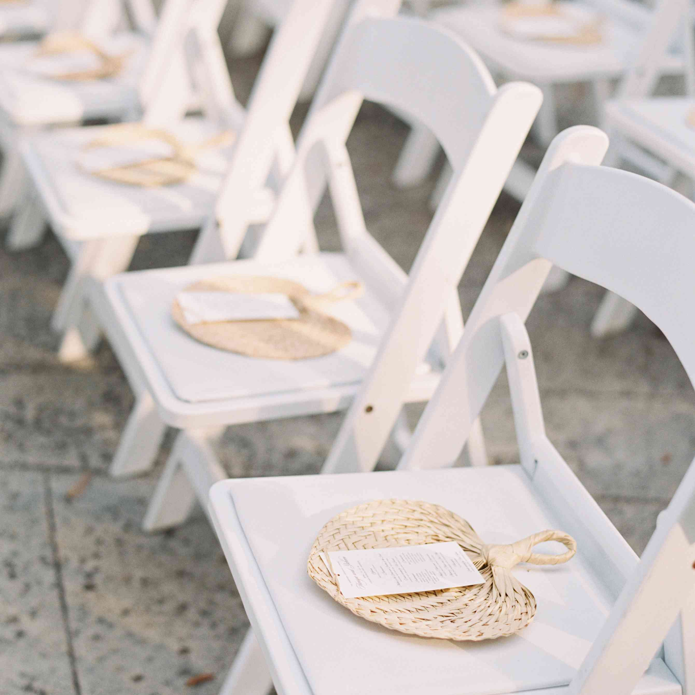 woven ceremony fans on white wooden chairs