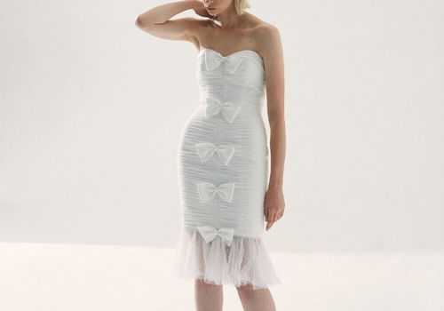 Model in strapless ruched mini dress with bows and tulle hem