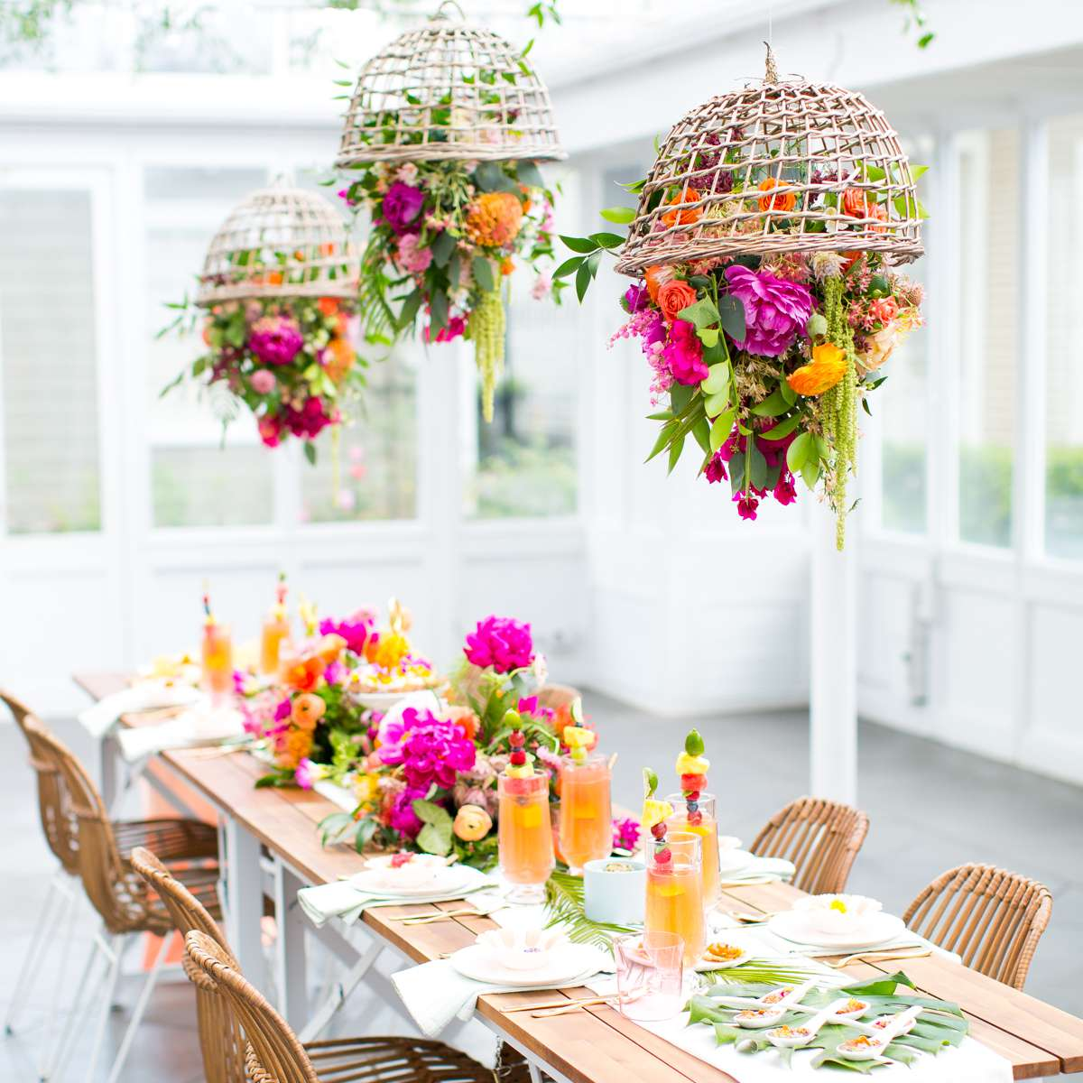 Hanging bright colored floral chandeliers above a set table