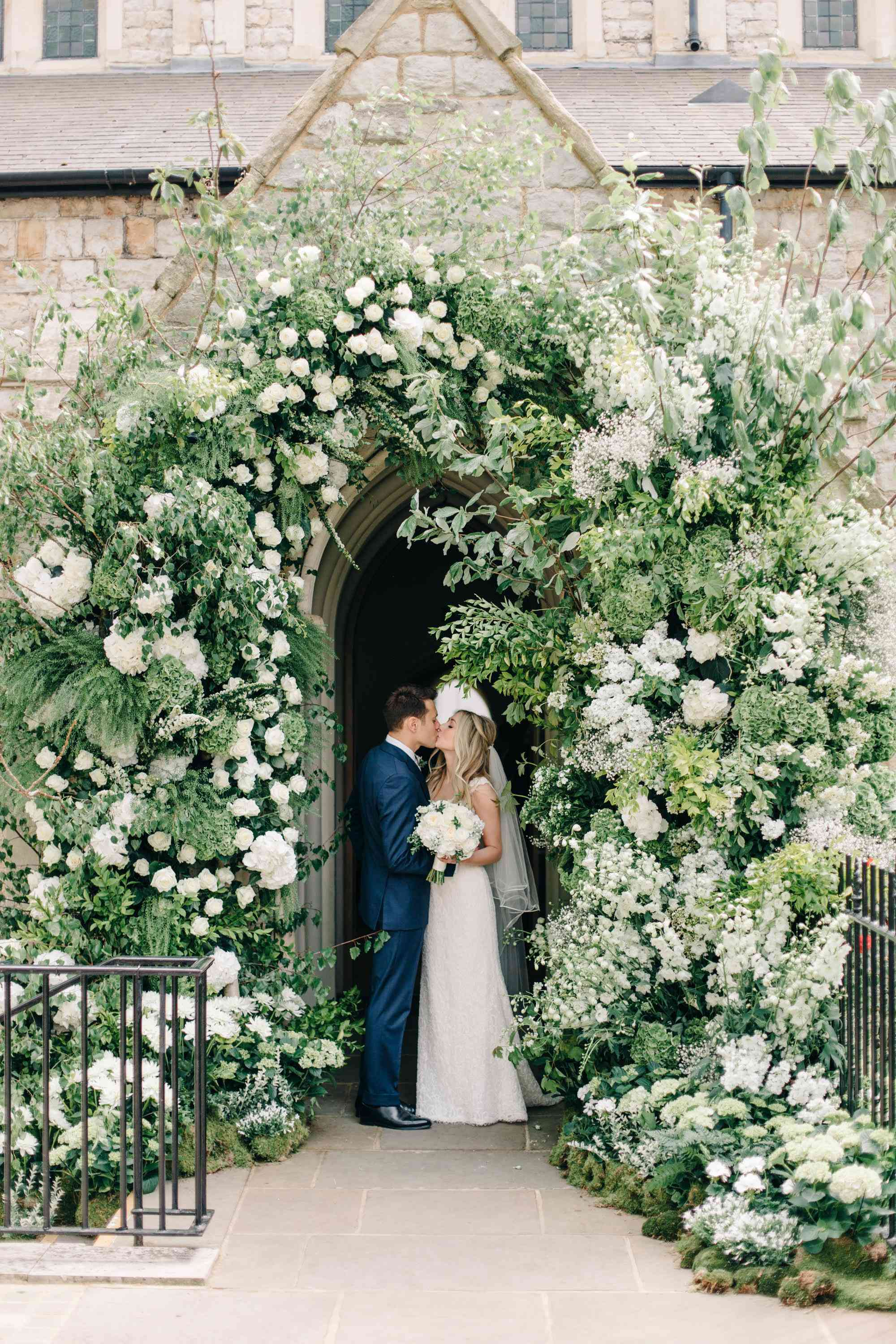 Bride and groom kissing under a floral decorated entryway